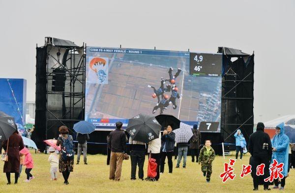下雨了跳伞比赛中断,观众打伞穿雨衣等天气晴